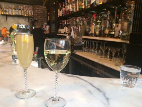 NYローワーイーストサイドにあるレストラン、バカロのバーカウンター。バーの上にはBELLINIピーチのお酒と白ワイン。