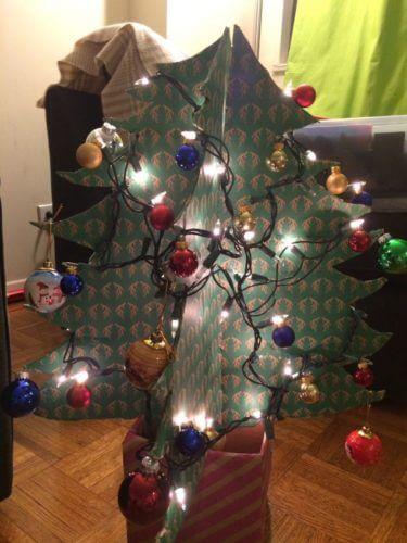 ダンボールで作ったクリスマスツリーに電球とオーナメントをつけた写真