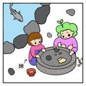 池の脇でクルミを石臼で挽く子供達
