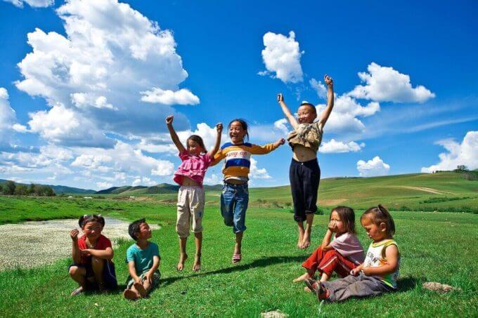 芝生の上でジャンプしている子供たち