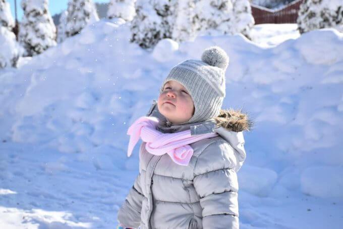 雪景色の中で満足そうな顔をしている赤ちゃん