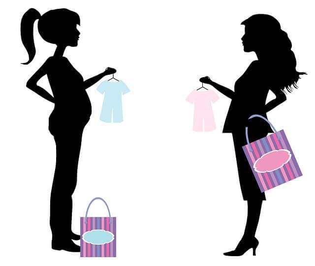 2人の妊婦が赤ちゃんの服を持っている影絵