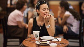 カフェで女性が美味しそうにクッキーを食べている写真