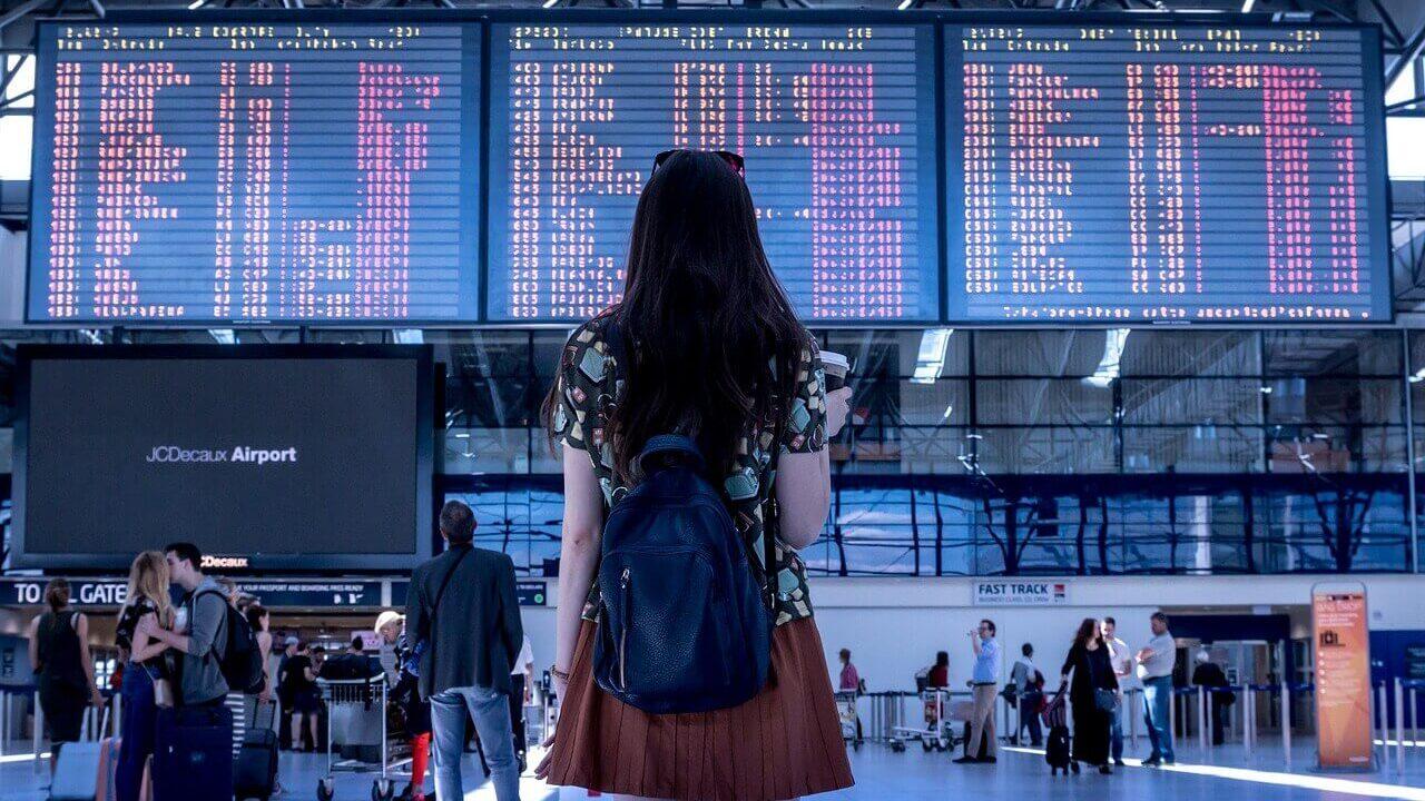 女性が空港で掲示板の前に立っている後ろ姿