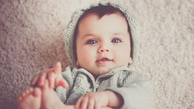 足を掴んで笑っている赤ちゃん