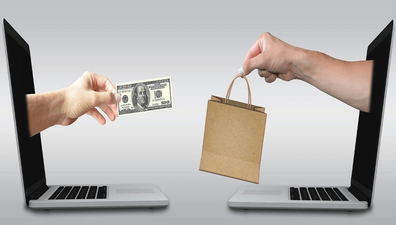 ネットで売り買いする人の手がパソコンから伸びている画像